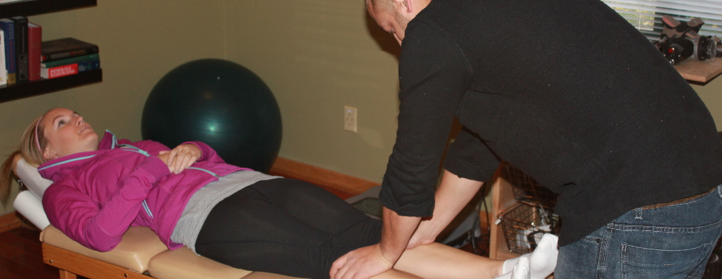 Client laying on the chiropractic table while Dr. Trimner works on her knees